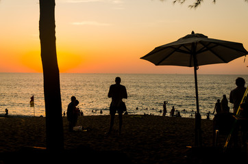 People family friend enjoying beautiful quiet calm sunset at a sandy beach with calm wave water and blue orange golden sky at an island resort marriage honeymoon vacation holiday