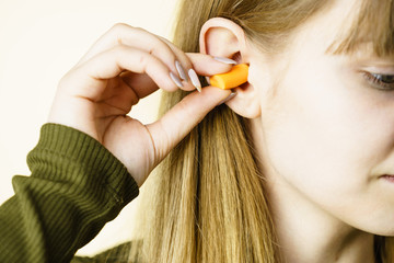 Woman putting ear plugs into ears