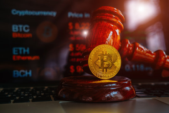 Law or auction gavel and bitcoins on a wooden desk, dark background, gavel and bitcoin symbol on brown table with copyspace. Bitcoin Currency Technology Business Internet Concept.
