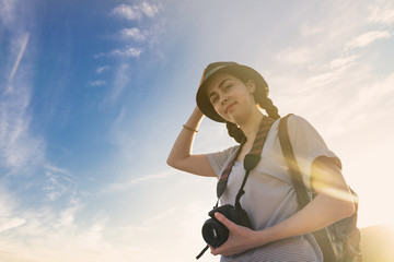 girl tourist with a backpack and a camera on the background of blue sky and sunset ,photos from the bottom up