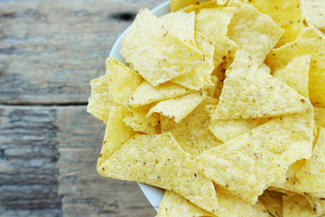 Nachos or corn tortilla chips on a bowl on rustic wooden background