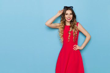 Beautiful Fashion Model In Red Dress Is Smiling And Looking At Camera