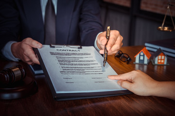 Partner lawyers or attorneys discussing a contract agreement. Successful businessmen hand putting signing contract,have a contract in place to protect it,signing of modest agreements form in office.