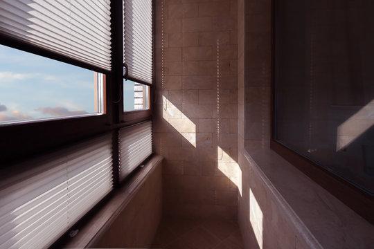 Dark balcony window with light blue cloud sky in partially open jalousie.