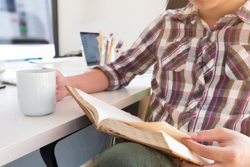 Businessman reading a book with coffee cup on hand closeup shot photo.