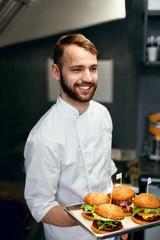 Chef With Burgers In Restaurant Kitchen