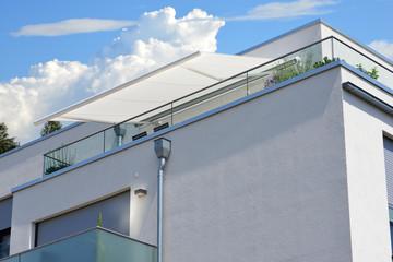 Moderne verglaste Balkone mit elektrischer Markise, Edelstahl-Geländer, Regenfallrohr und Dachrinne an Neubau-Hausfront
