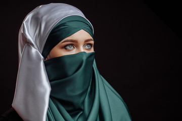 close up side view shot of pretty model in Islamic clothes looking up.copy space