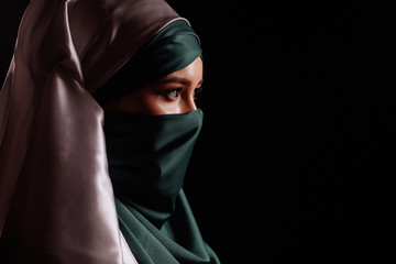 side view shot of eastern beautiful woman with pensive look in satin hijab
