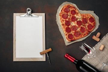 Heart shaped pizza with mozzarella, sausagered, wine bottle and tablet on rusty background