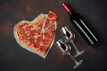 Heart shaped pizza with mozzarella, sausagered and wine bottle. Valentines day greeting card on rusty background
