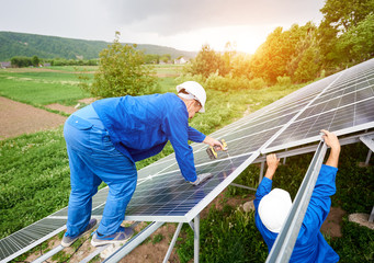 Construction worker connects photo voltaic panel to solar system using screwdriver. Professional installing and construction of solar system, alternative energy and financial investment concept.