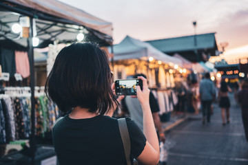 Asian woman taking photo with smartphone