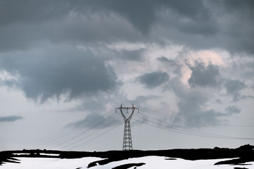 Power line tower standing on a mountain in Norway in front of a dramatic sky