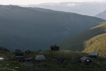 Rural cabins overlooking a mountain valley in Norway during sunset