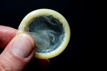Männerhand hält ein Kondom bereit, schwarzer Hintergrund
