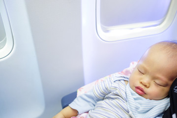 Adorable Baby Boy Sleeping On Airplane with copyspace,Toddler boy sleeping on mother's laps while traveling in airplane,Flying with children. Mom and sleeping 10 months old baby:Shallow depth of field