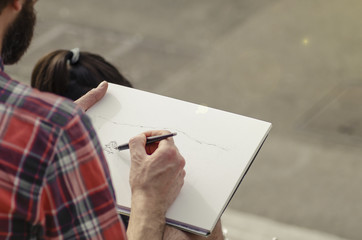 Man painting a landscape on a piece of paper