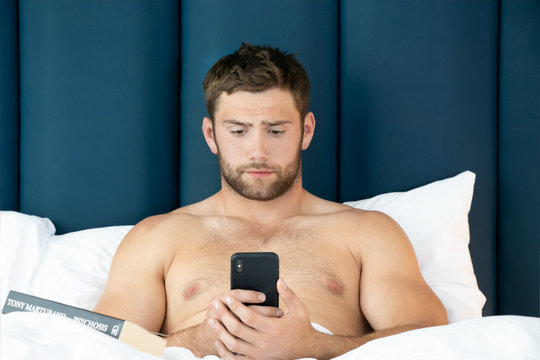 Shirtless sexy hunky man with beard lies naked in bed using mobile phone