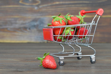 Strawberries in a shopping cart on wooden background