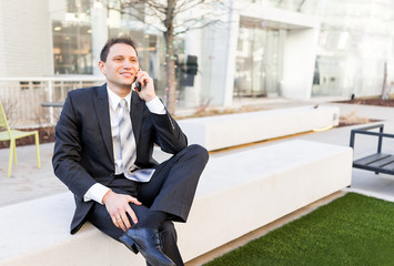 Handsome, attractive young businessman sitting on bench, using talking holding smartphone phone mobile cellphone smiling in suit and tie, cheerful on interview break in park