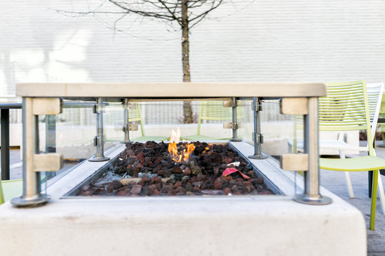 Fire pit in outside park with orange red flame, nobody, modern chairs in winter, coal, trash for warming hands on cold day
