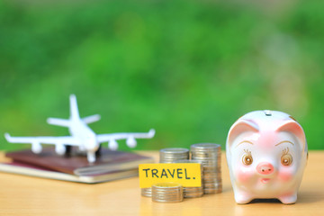 Saving planning for Travel budget of holiday concept, piggy bank and airplane on passport with natural green background