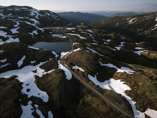 Car driving along a mountain road with lake nearby in Norway during sunset