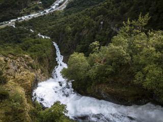 Aerial of a roaring powerful waterfall through a forest fjord valley in Norway