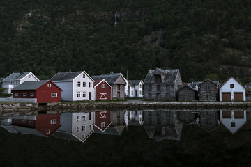 Rural houses reflected in a lake in front of a forest and waterfall in Norway