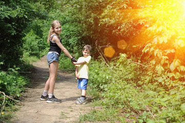 Young beautiful girl in shorts walking with her younger brother in the park. The little boy is also dressed in denim shorts
