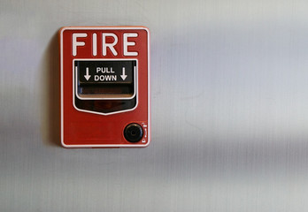 Manual fire alarm pull station on brushed steel wall