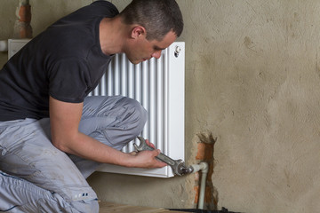 Young handsome professional plumber worker installing heating radiator on brick wall using a wrench in an empty room of a newly built apartment or house. Construction, maintenance and repair concept.