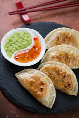 Close-up of pan fried korean potstickers served with dipping sauces, vertical shot, selective focus