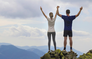 Back view of young couple, athletic boy and slim girl standing with raised arms on rocky mountain top enjoying breathtaking summer mountain view. Tourism, traveling and healthy lifestyle concept.