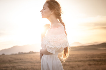 red-haired girl in a field of wheat in a white dress smiles a lovely smile