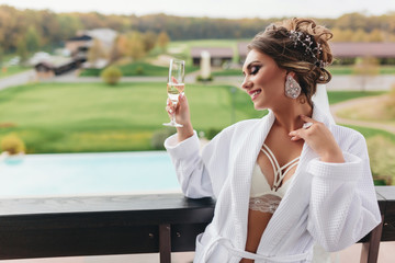 sexy woman in a dressing gown with a glass of drink, gently touching her neck