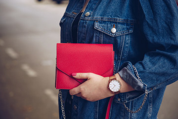 stylish woman in polka dot culottes and denim jacket holding a red purse and wearing a rose gold wrist watch.  street style fashion