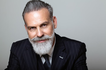 Portrait of attractive middle aged bearded gentleman wearing trendy suit over empty gray background. Studio shot, business fashion concept.