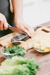 Woman cutting raw fish in the kitchen.