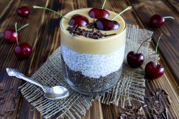 Pudding with chia,cherry and peanut paste on the rustic  wooden background
