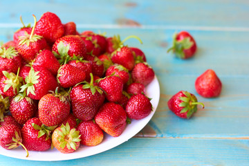 A plate of strawberries on a wooden table.
