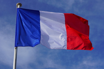 A French flag with blue, white and red stripes