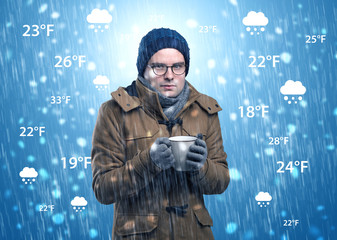 Young man freezing in warm clothing with weather condition and forecast concept