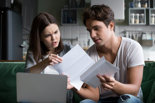 Frustrated wife shocked by bad news, high taxes, final notice past due debt reading mail paper letter from bank with husband at home, millennial couple angry with financial problems, domestic bills