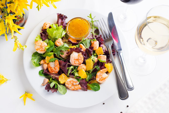 Healthy salad with prawns, lettuce, oranges and mango served on a plate with orange mustard sauce