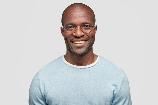 Middle aged cheerful dark skinned male with shining smile, wears light blue sweater, round spectacles, achieves everything by himself, stands against white studio wall, has relaxed face expression