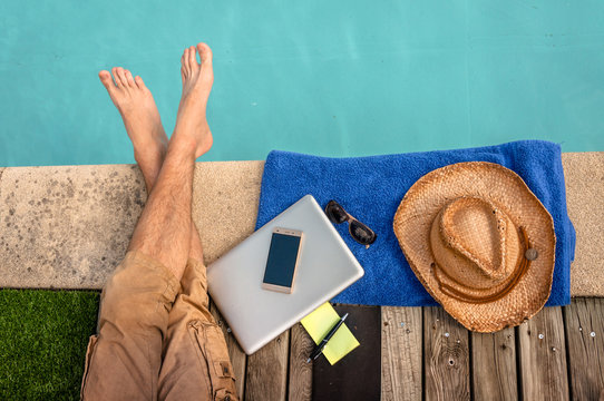 Man relaxing near swimming pool with computer