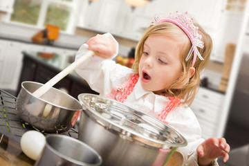 Cute Baby Girl Playing Cook With Pots and Pans In Kitchen