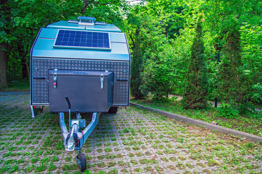 Solar panel is fixed on the tourist trailer. Off-road trailer stands in the parking lot on the background of thick green foliage.